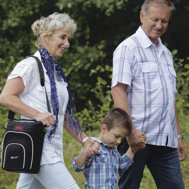 Woman with Zen-O-Lite portable oxygen device walking with family
